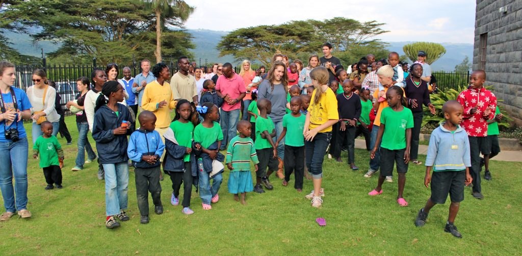 Ruth (center, green sweater) being led across the Naomi's Village yard for the very first time.